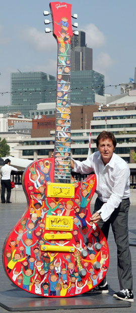 Sir Paul McCartney and his 10 foot hand painted Gibson Les Paul on site at the Gibson Guitartown London charity exhibition