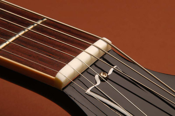 The Nut: If you hear a tink when tuning, the nut slots are too narrow and the string is binding.