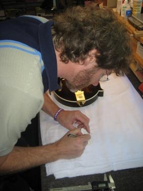 Sam Bush signing contest winner's mandolin
