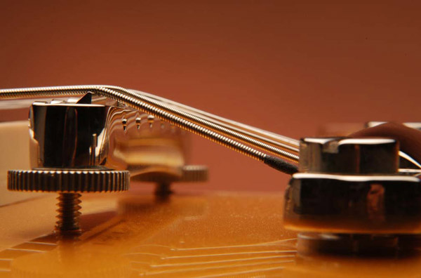 The Tailpiece: If the guitar has a stop or trapeze tailpiece, it should rest at a height that provides for a good break angle over the bridge without allowing the string to make contact with the back side of the bridge.